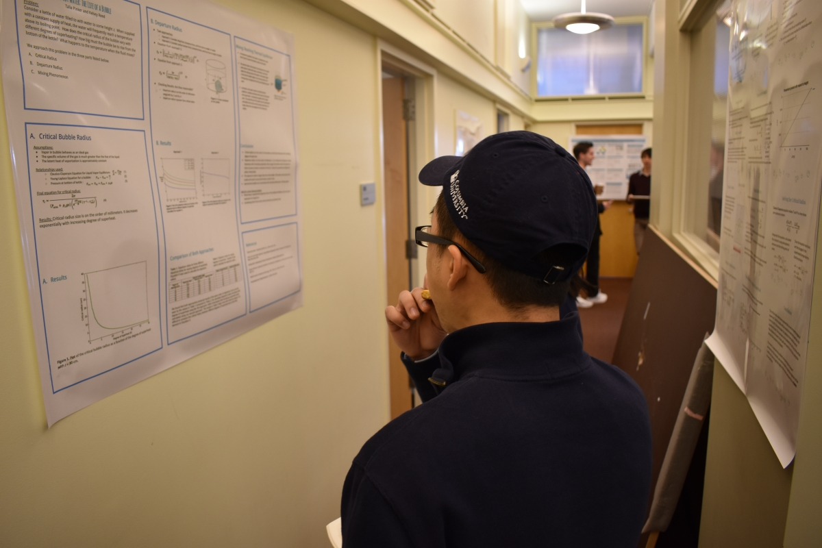 a student looking at a poster
